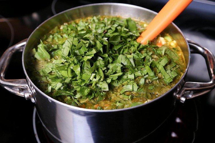 Добавляем нарезанные листья щавеля в зеленый борщ